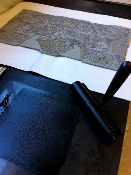 Rolling the ink ready to print the linoblock